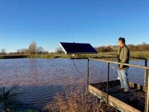 man standing beside a lake